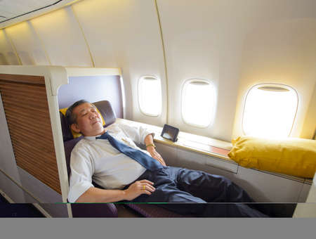 Business man sleeping at the first class of airplane in comfortable single seat Stock fotó