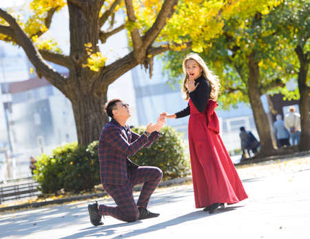 Man on his knees makes a proposal to marry the woman
