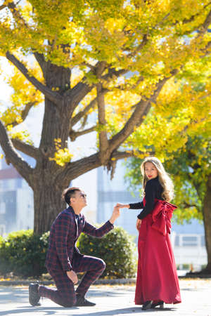 Asian man on his knees makes a proposal to marry the woman