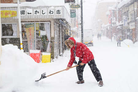 Takayama, Japan - January 16,2017 : Old japanese man with snow shovel removing snow on the road in winter time at Takayama old town 報道画像