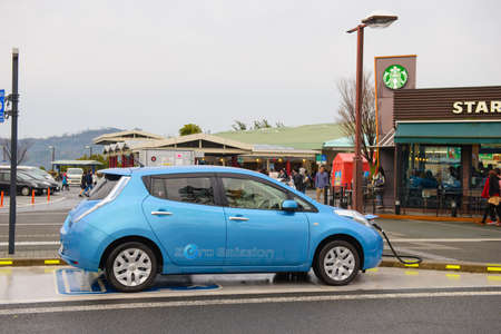 Nagoya, Japan - March 29, 2015 : Electric car Nissan Leaf is being charged at the charging station Editorial