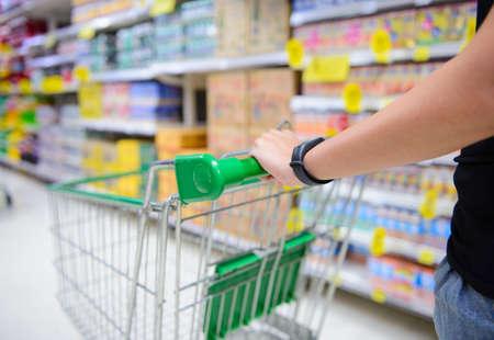 Closeup hand pushing shopping cart in groceries store