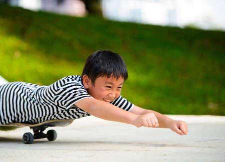 Little asian boy lying on a skateboard