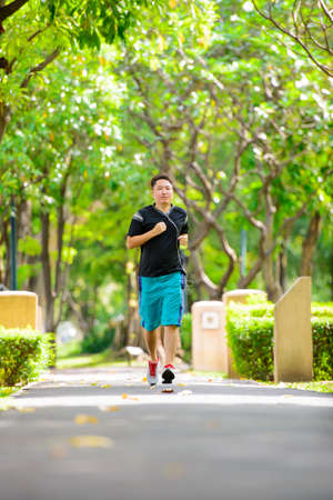 Young man in sports clothing jogging in park with headphone Imagens