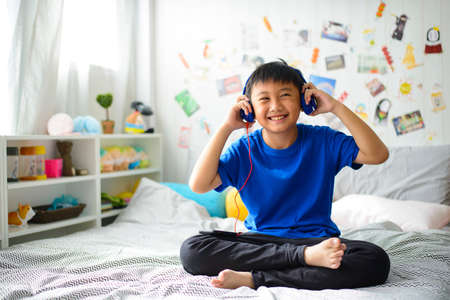 Little asian boy using headphones and smiling happy while listening music Stock Photo