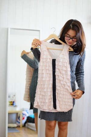 Une femme asiatique choisit des robes devant un miroir