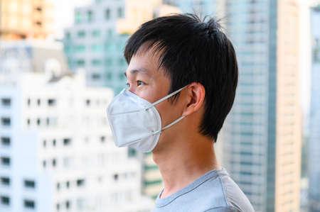 Asiatischer Mann trägt Maske für Luftverschmutzung