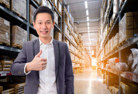 Asian man in suit showing thumbs up gesture over warehouse background Stock Photo