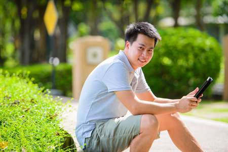 Young asian man with tablet in the park Stock Photo