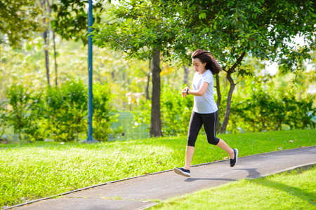 Young asian woman running in a city park and looks at the smart watch