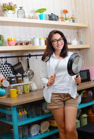 Young asian woman showing a pan and a spatula in kitchen