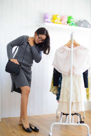 Young asian woman trying on shoes with black leather bag