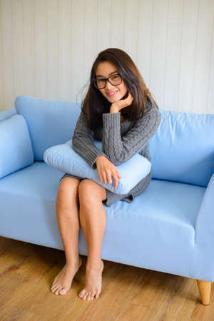Asian woman sitting on blue sofa with pillow in hands