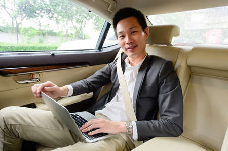 Successful young man using laptop while sitting in car Stock Photo