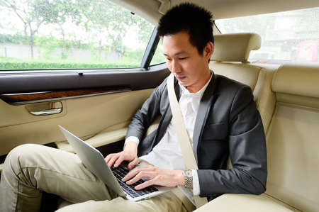 Young businessman using laptop on the backseat of a car Stock Photo