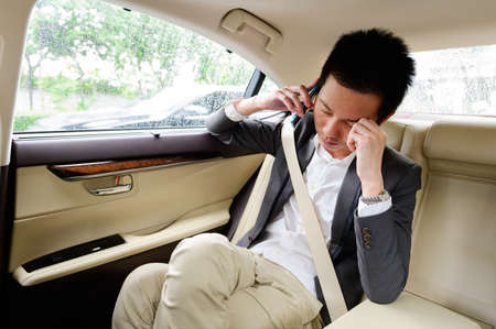 Stressed frustrated businessman talking on phone in the car