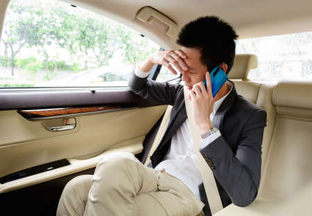 Stressed businessman calling on a mobile phone in the car Reklamní fotografie