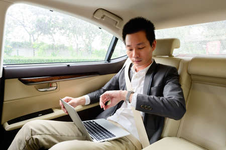 Handsome businessman checking time and working with laptop in car