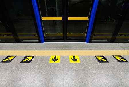 Yellow arrow marks on the floor of subway platform
