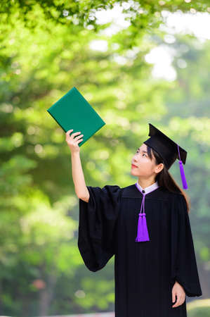 Pretty asian female holding diplomas 写真素材