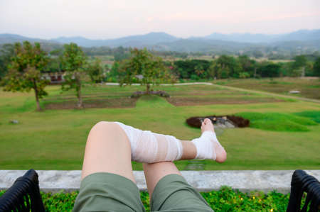 Man resting outdoor on a grass field with bandage legs