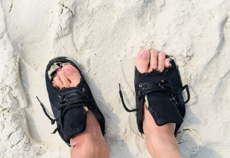 Old worn shoes on feet with human finger in holes