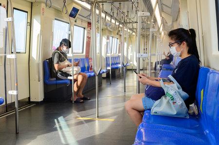 Bangkok, Thailand - May 2, 2020 : Passenger inside subway train wear mask keep distance protect from covid-19 virus
