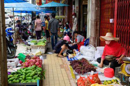 Hat Yai, Thailand - August 6, 2020 : Thai people wear surgical mask buying a fruit at Hat Yai Plaza Market
