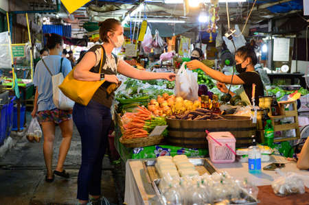 Bangkok, Thailand - August 5, 2020 : People wear surgical mask buy vegetables at fresh market Redactioneel