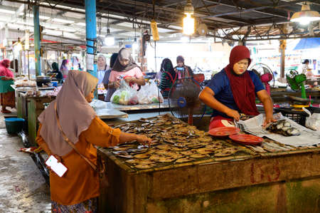 Hat Yai, Thailand - August 6, 2020 : Unidentified muslim seller prepare dried fish for customer at Hat Yai Market
