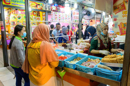 Hat Yai, Thailand - August 6, 2020 : Thai people wear surgical face mask while buying food from muslim seller Editorial