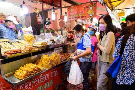 Bangkok, Thailand - August 14, 2020 : Crowd of people wear surgical mask walking to buy food at Wang Lang Market
