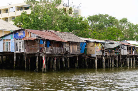 Bangkok, Thailand - August 14, 2020 : Wooden slums on stilts on the riverside of Chao Phraya River in Bangkok