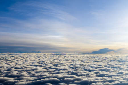 Above sunrise clouds from airplane window