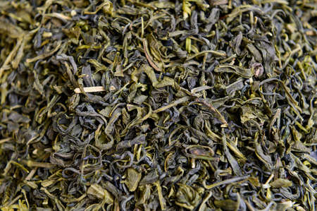 Dried green tea leafs background Imagens