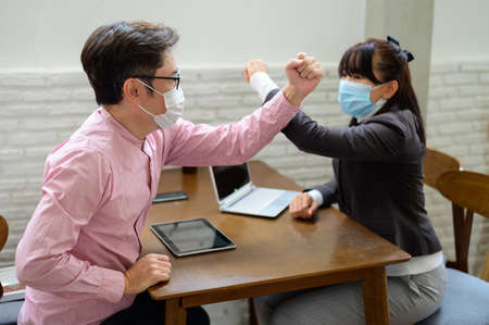 Coworkers with protective masks making elbow bump in office