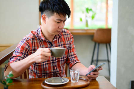 Young asian man using smartphone and having coffee