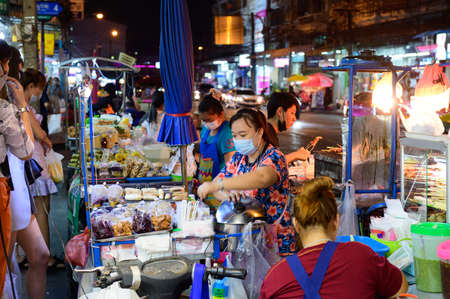 Bangkok, Thailand - January 30, 2021 : Street vendors with protective mask during the covid-19 Editorial