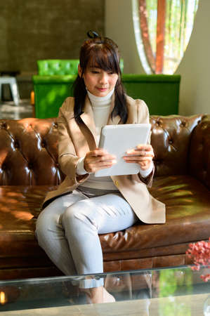 Young woman holding tablet and using video conference