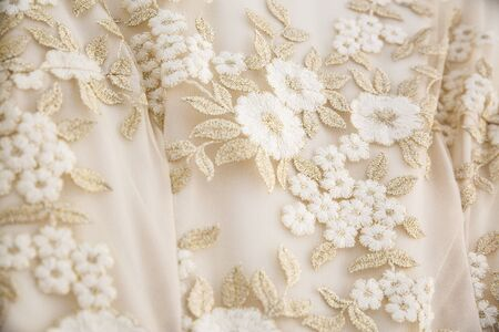 detail of a wedding dress with embroidered flowers