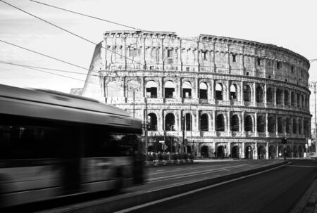 Rome Colosseum with buses moving in city traffic, travel reportage