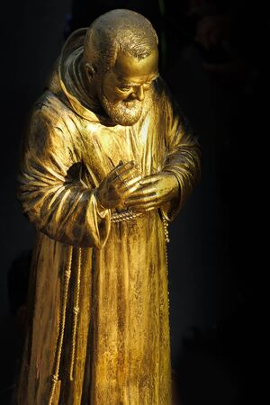 A golden statue of the Saint Padre Pio of Pietrelcina. Banco de Imagens