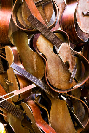 Broken and stacked acoustic guitars create an artistic background Zdjęcie Seryjne