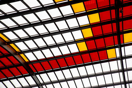 Roof with colored windows of red white and yellow generates a geometric texture