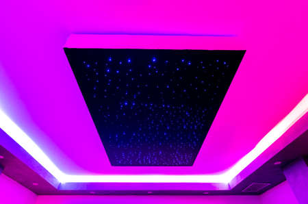 ceiling of a spa center with colored lights and geometric perspective
