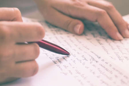 hands holding a pen while writing a letter