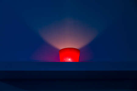 red candle on blue background inside a spa