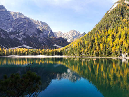 Italy, Trentino Alto Adige: natural landscape of Braies Lake with green trees, lake with reflection and mountain with snow