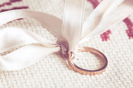 details of a wedding ring with white ribbon and laid on an embroidered fabric