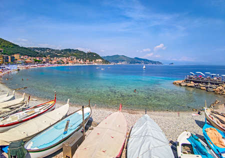 Italy, landscape of the Ligurian coast at noli, beach with tourists and boats moored on the beach.